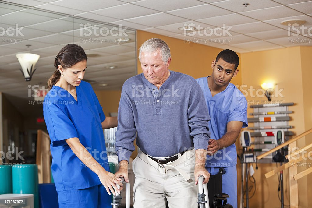 Healthcare workers helping senior man use walker stock photo