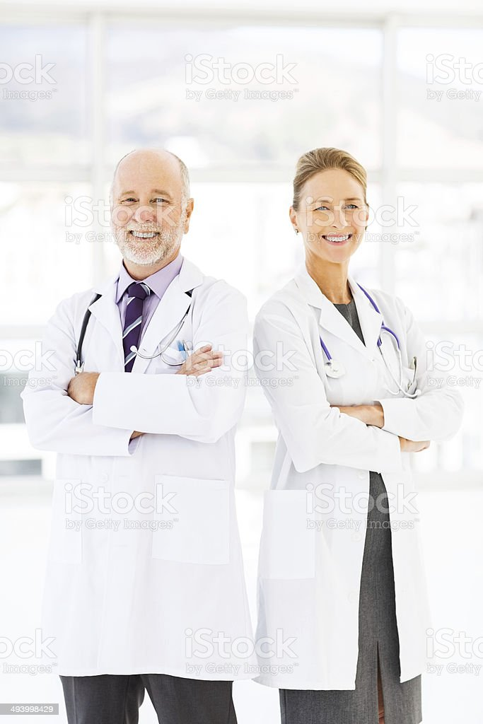 Healthcare Workers Standing Arms Crossed In Hospital stock photo