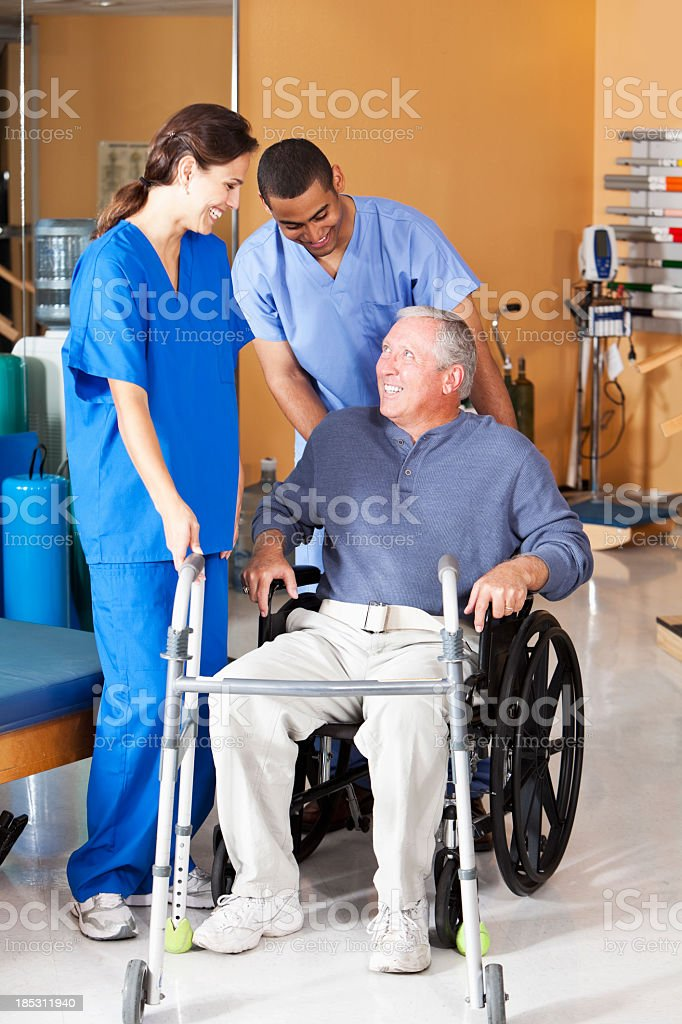 Healthcare workers with senior man in wheelchair stock photo