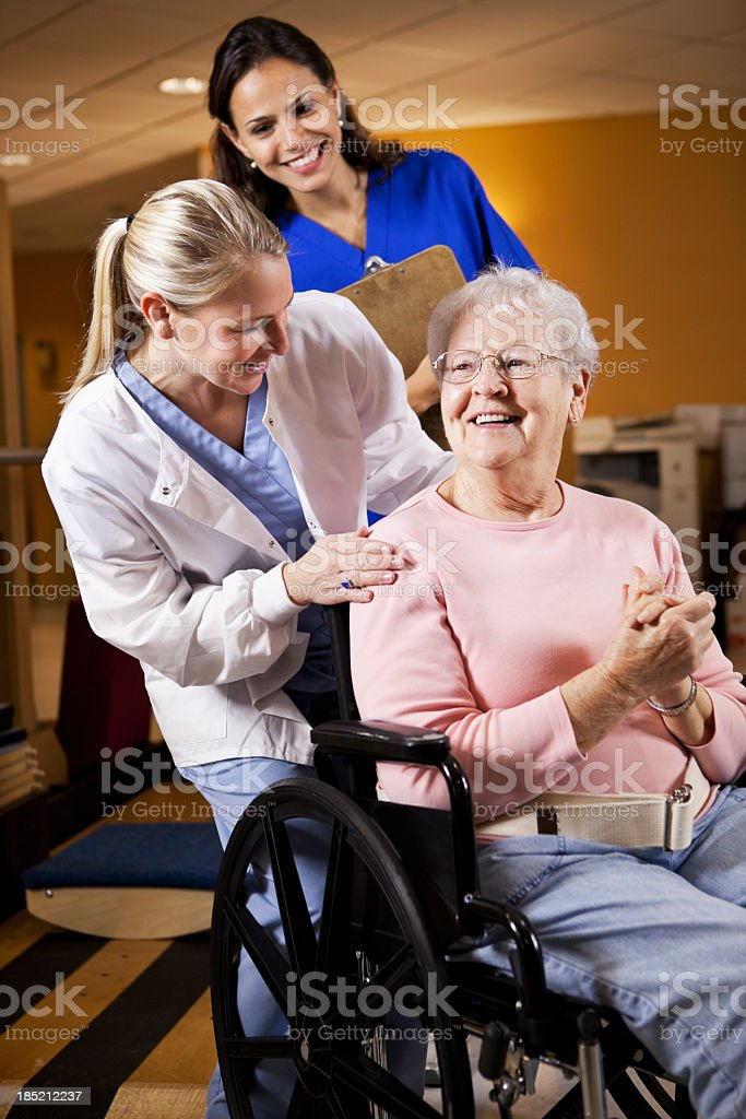 Healthcare workers with senior woman in wheelchair stock photo