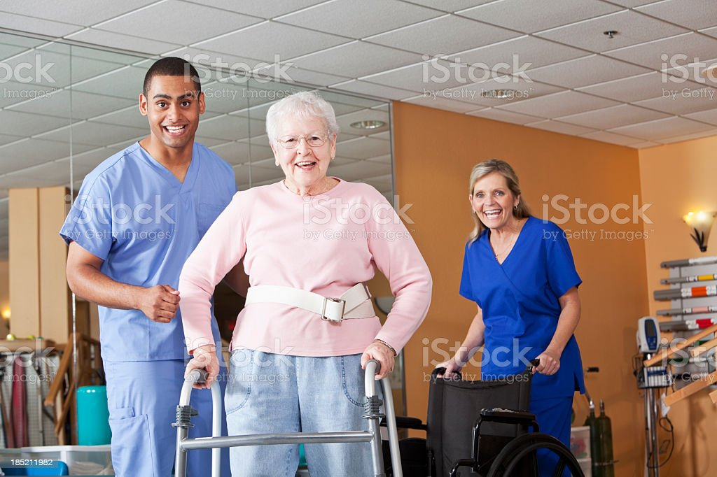 Healthcare workers with senior woman using walker stock photo