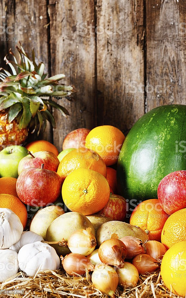 Healthful collection of winter fruits and vegetables against wood stock photo