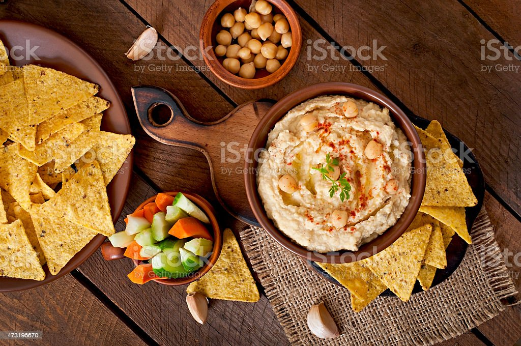 Healthy arrangement of hummus, vegetables, and pita chips stock photo