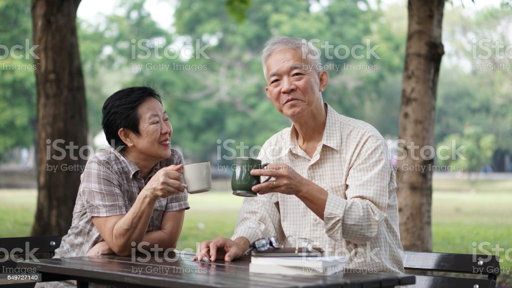 Healthy Asian senior couple drinking coffee in morning park together stock photo