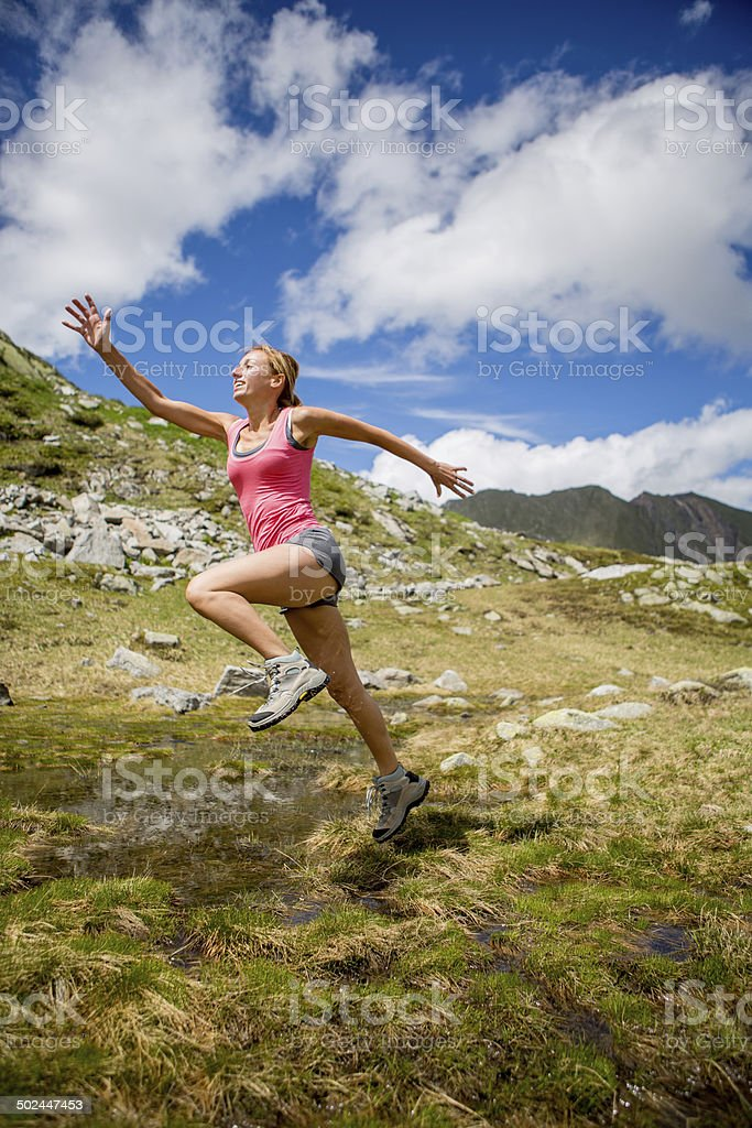 Healthy athletic woman jumping in nature stock photo