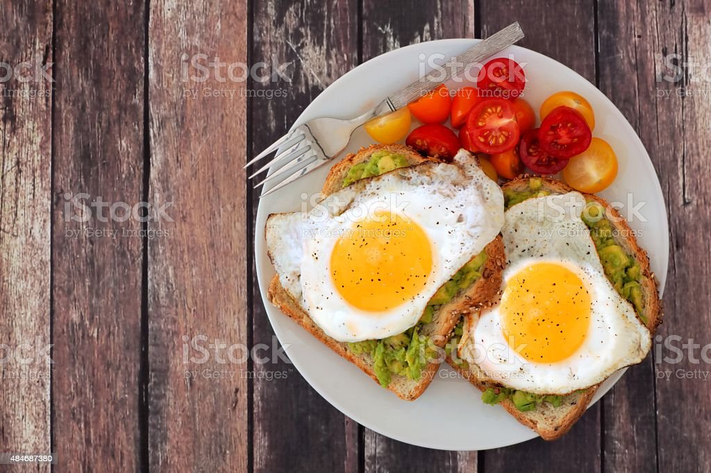 Healthy avocado, egg toasts with tomatoes on rustic wood background stock photo