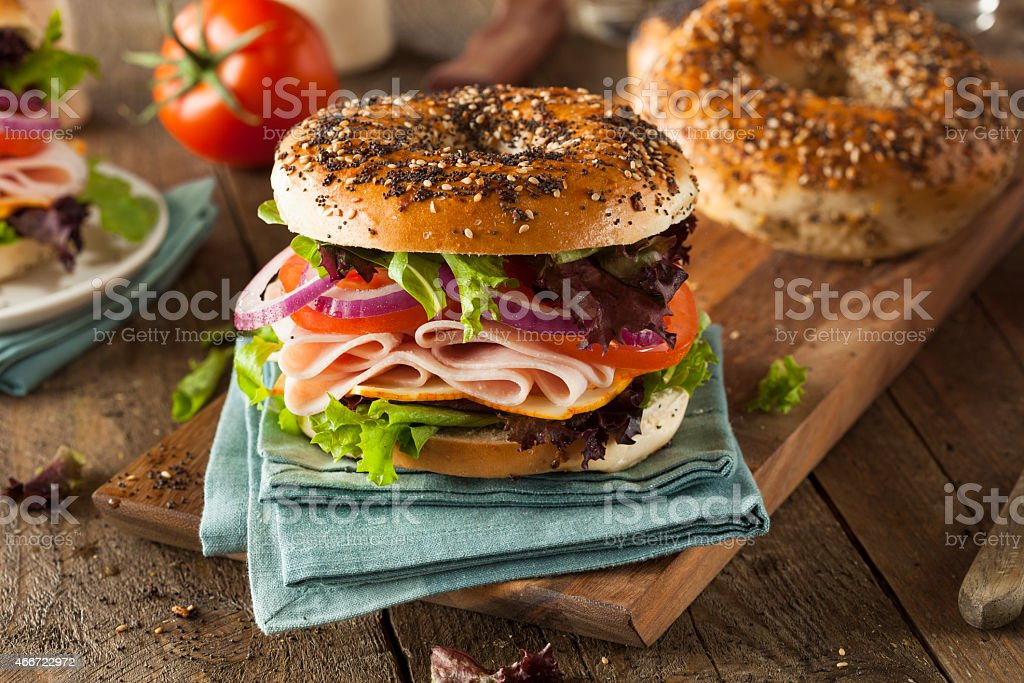 Healthy bagel with turkey and salad on a rustic table stock photo