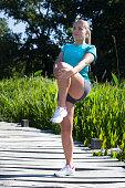 healthy blond girl stretching her legs on wooden bridge, summer