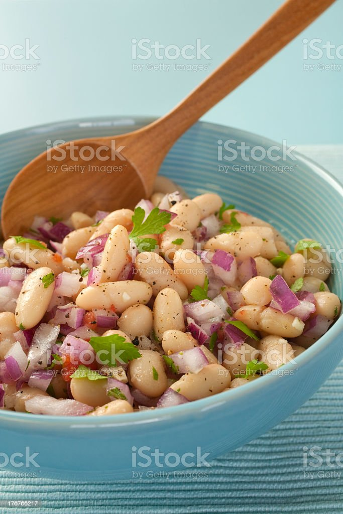 A healthy bowl of bean salad with wooden spoon stock photo