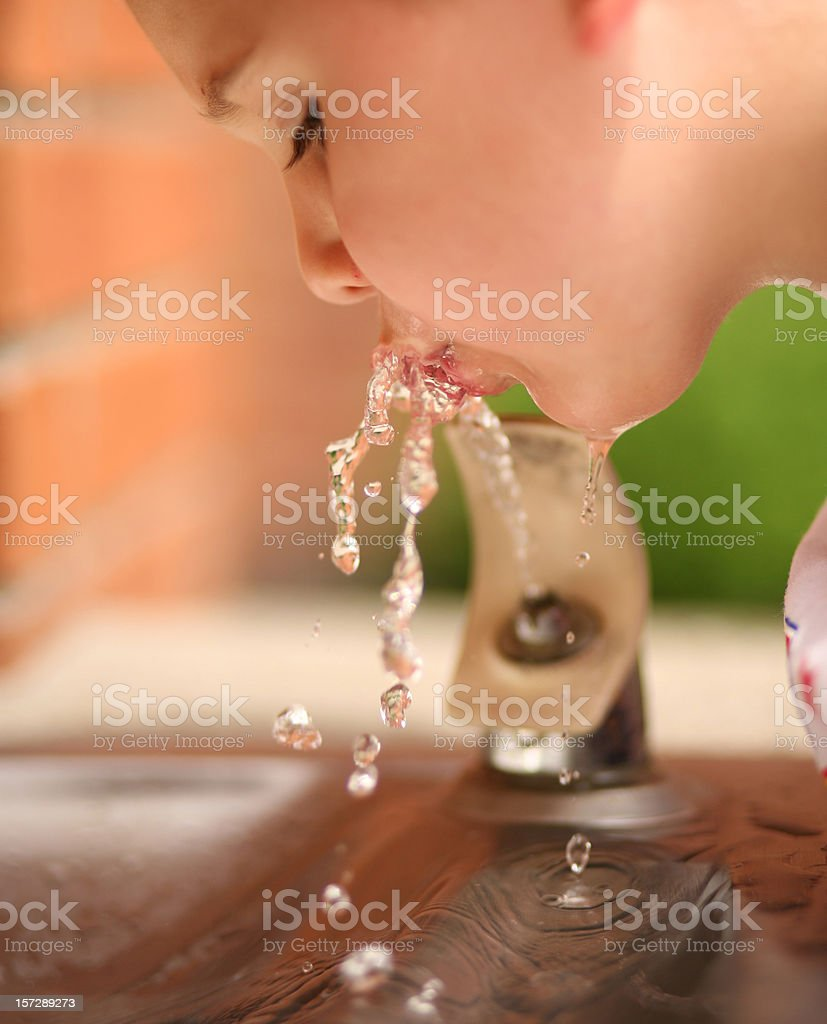 Healthy Boy Drinking Water at Fountain stock photo