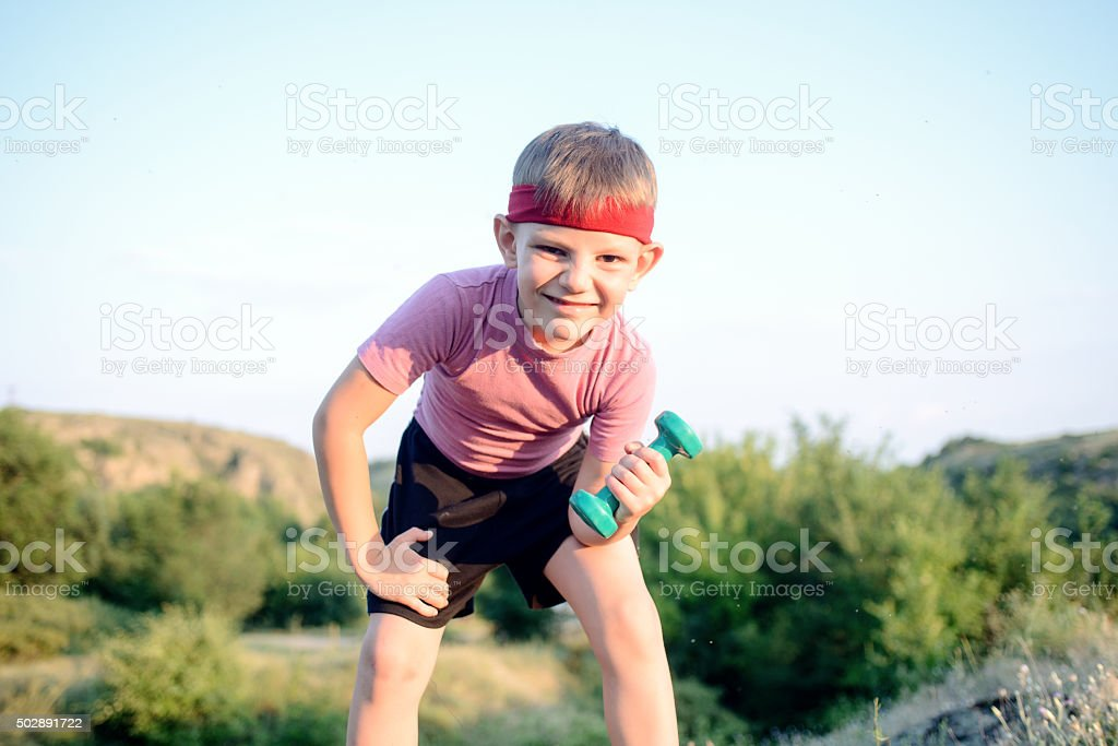 Healthy Boy Leans Forward While Lifting Weights stock photo
