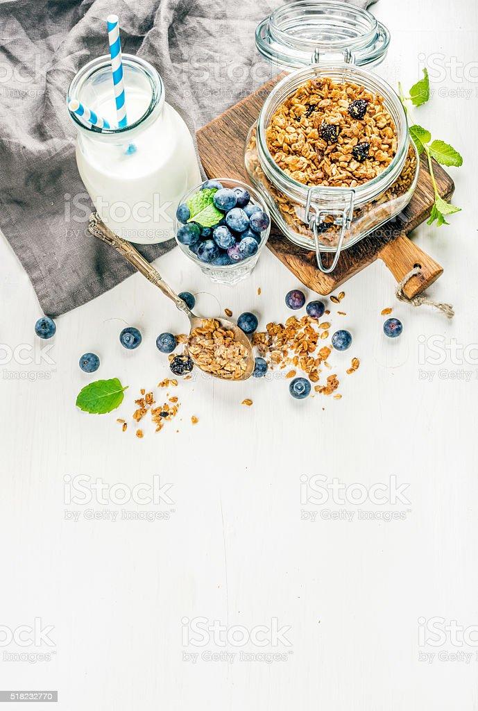 Healthy breakfast ingrediens. Homemade granola in open glass jar, milk stock photo