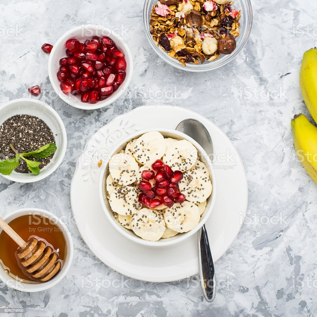 Healthy breakfast oatmeal with pomegranate, bananas, seeds and nuts, overhead stock photo