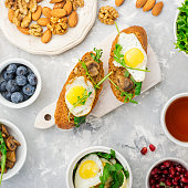 Healthy breakfast with fried eggs, fresh bread, salad, berries, tomatoes
