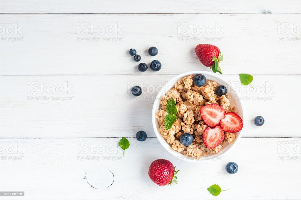 healthy breakfast with muesli and berries, top view, flat lay stock photo
