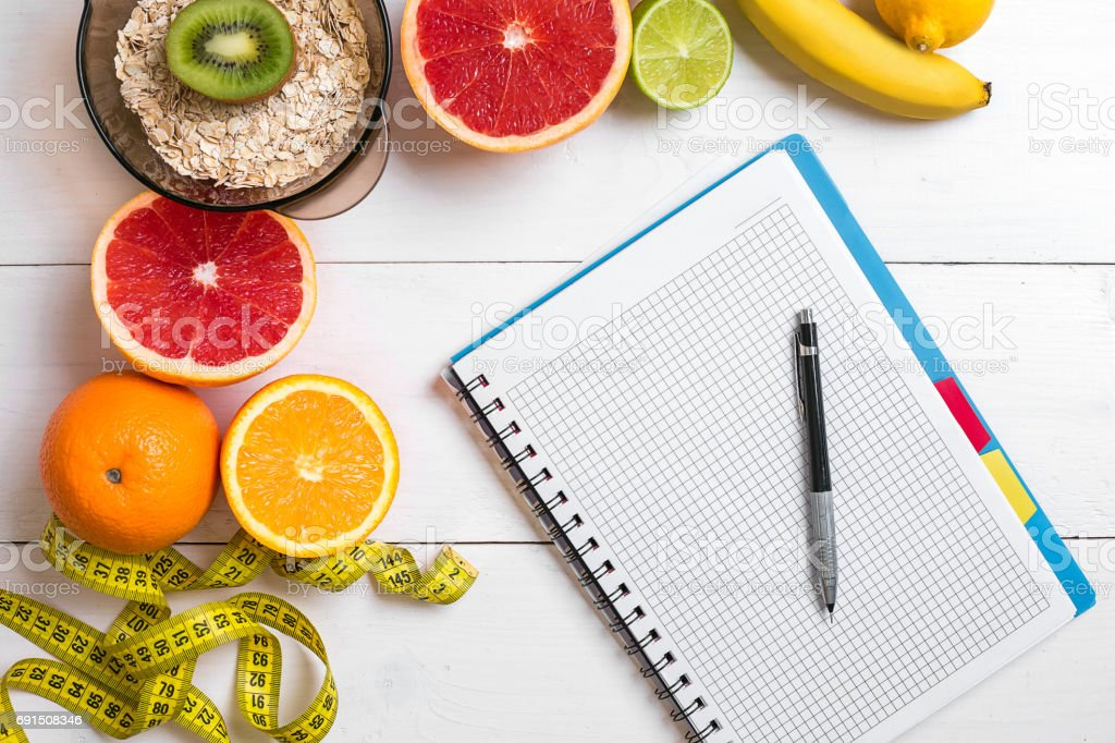 Healthy breakfast with oatmeal, fresh fruits and notebook on rustic wooden table stock photo