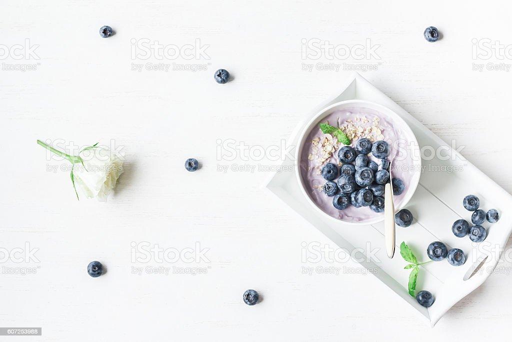 Healthy breakfast with yogurt, muesli and blueberry. Flat lay stock photo