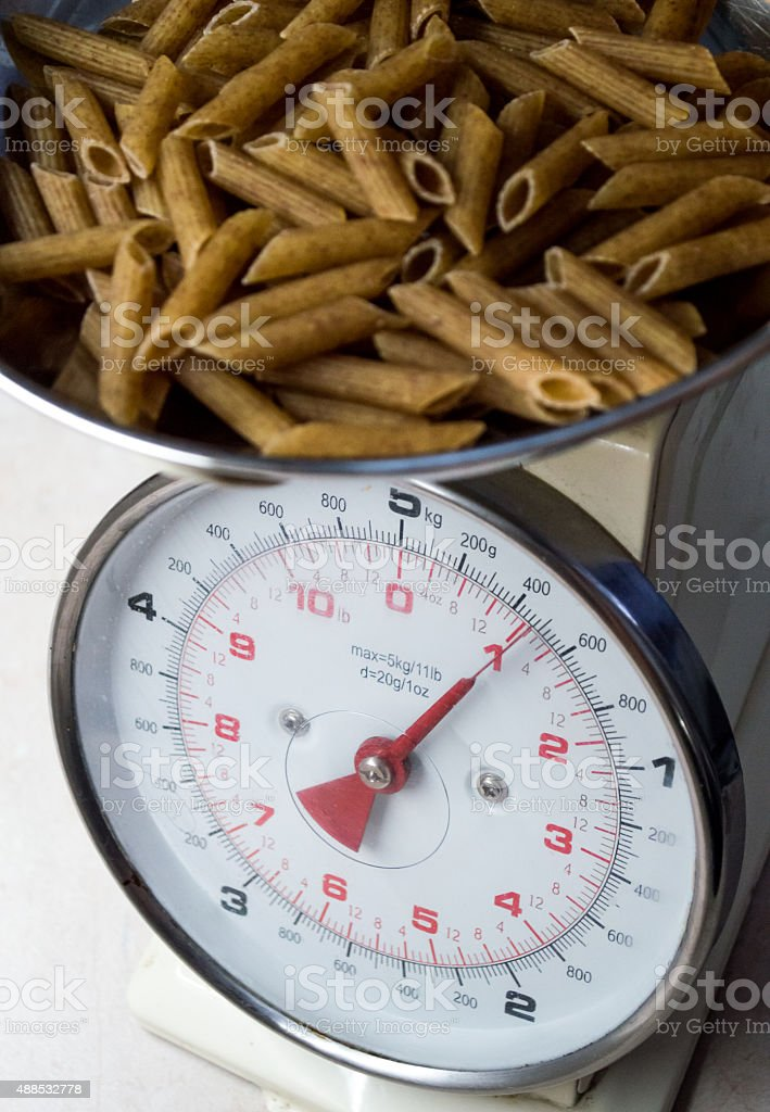 Healthy Brown Wholewheat Pasta Weighed on a Kitchen Scale royalty-free stock photo