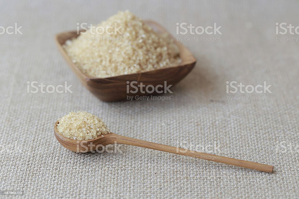 Healthy cane sugar on old wooden spoon stock photo