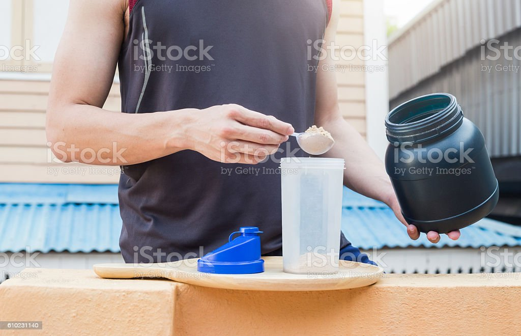 Healthy concept, man pour whey powder on the bottle. stock photo