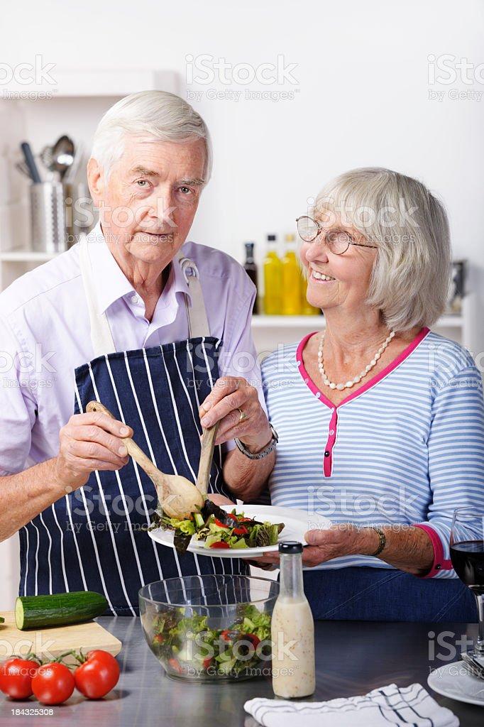 Healthy Conscious Senior Couple Dishing Salad stock photo