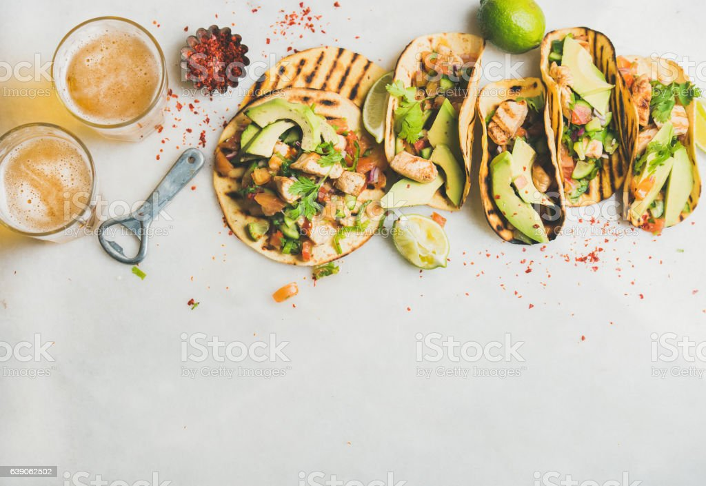 Healthy corn tortillas with grilled chicken, avocado, lime, beer stock photo