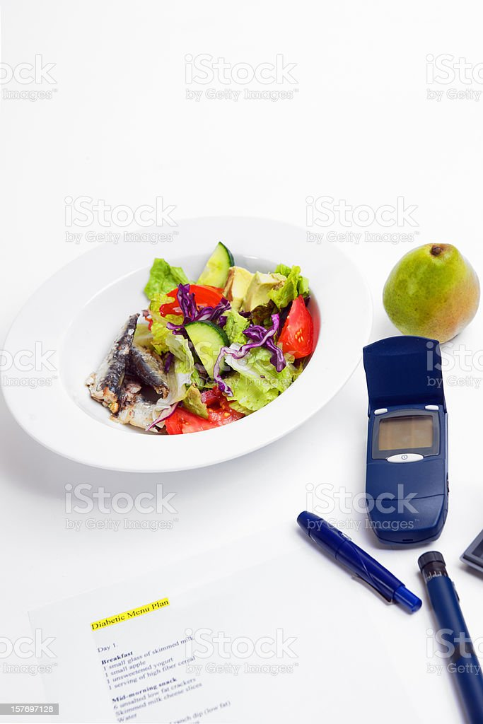 Healthy diabetic meal and blood sugar tester stock photo