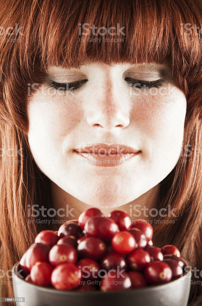 Healthy eating. Pretty redhead woman with bowl of fresh cranberries. royalty-free stock photo