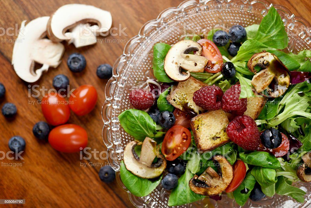 Healthy eating - salad with berries, mushrooms, and tofu stock photo