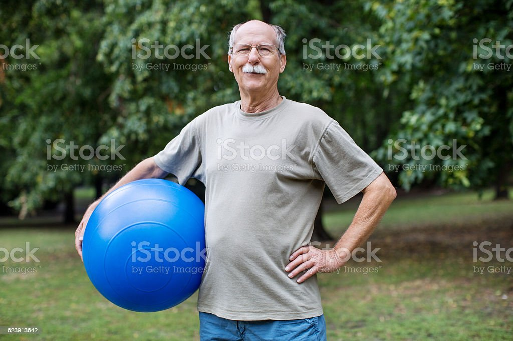 Healthy elder man at park with pilates ball stock photo