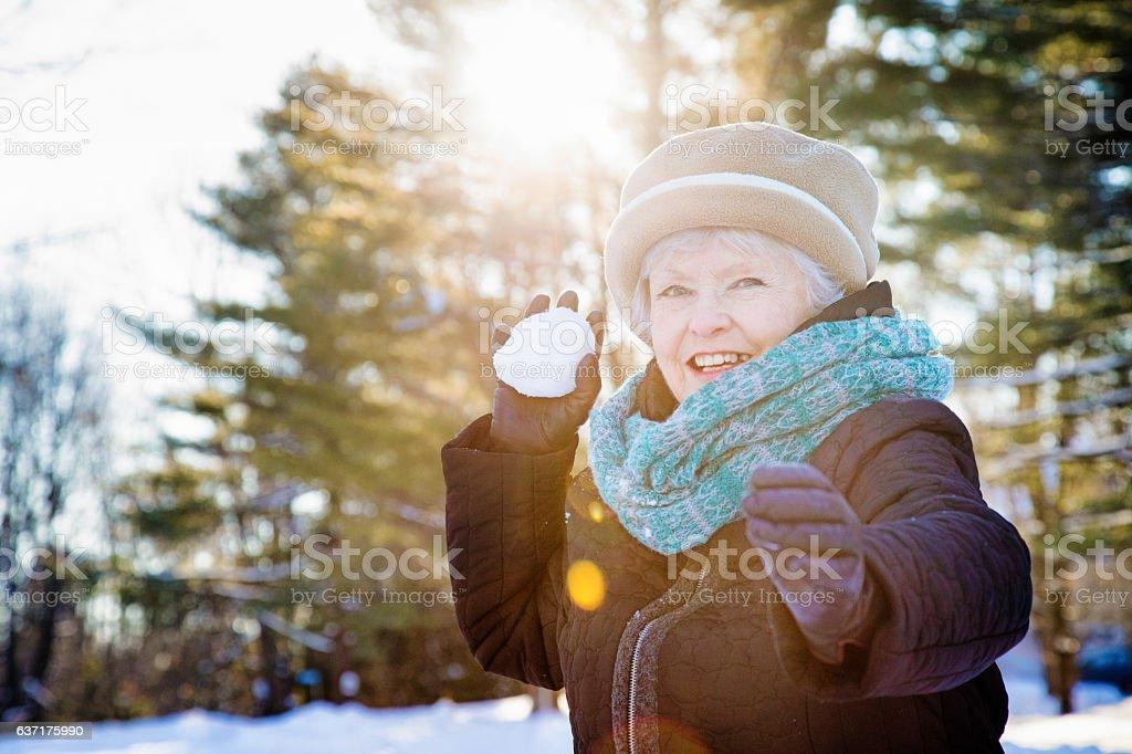 Healthy energetic senior woman throwing snow ball stock photo