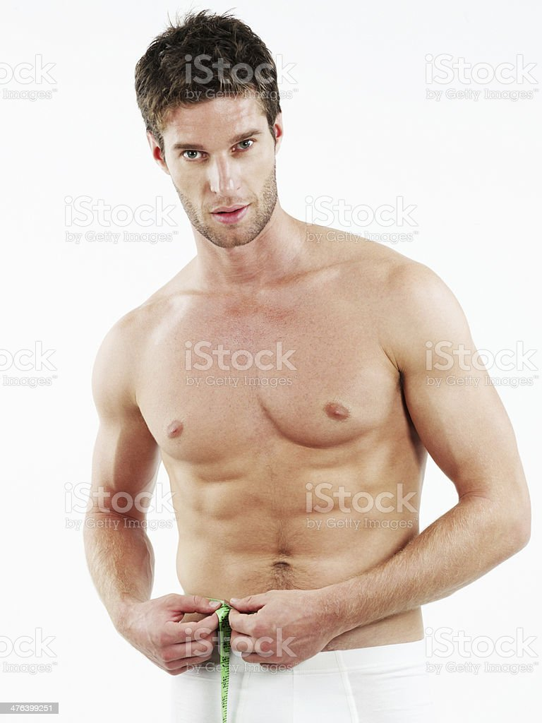 Healthy fit man with green measuring tape royalty-free stock photo