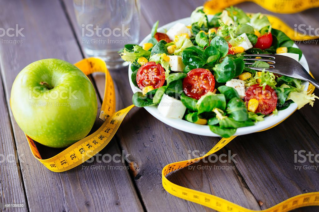 Healthy fitness green salad and apple stock photo