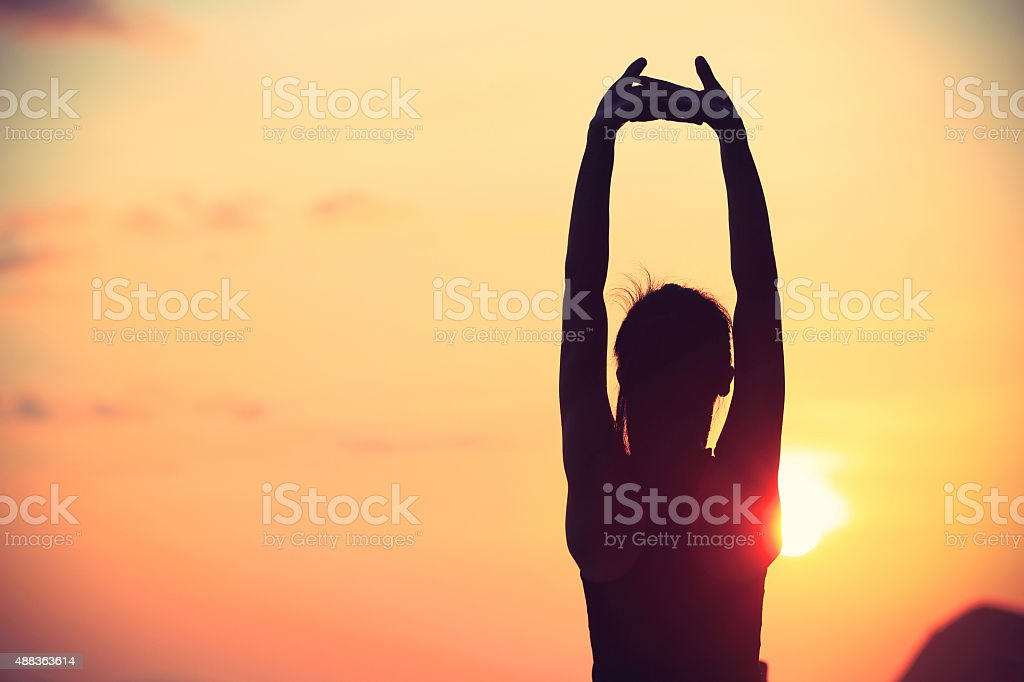 healthy fitness yoga woman stretching arms at sunrise seaside stock photo