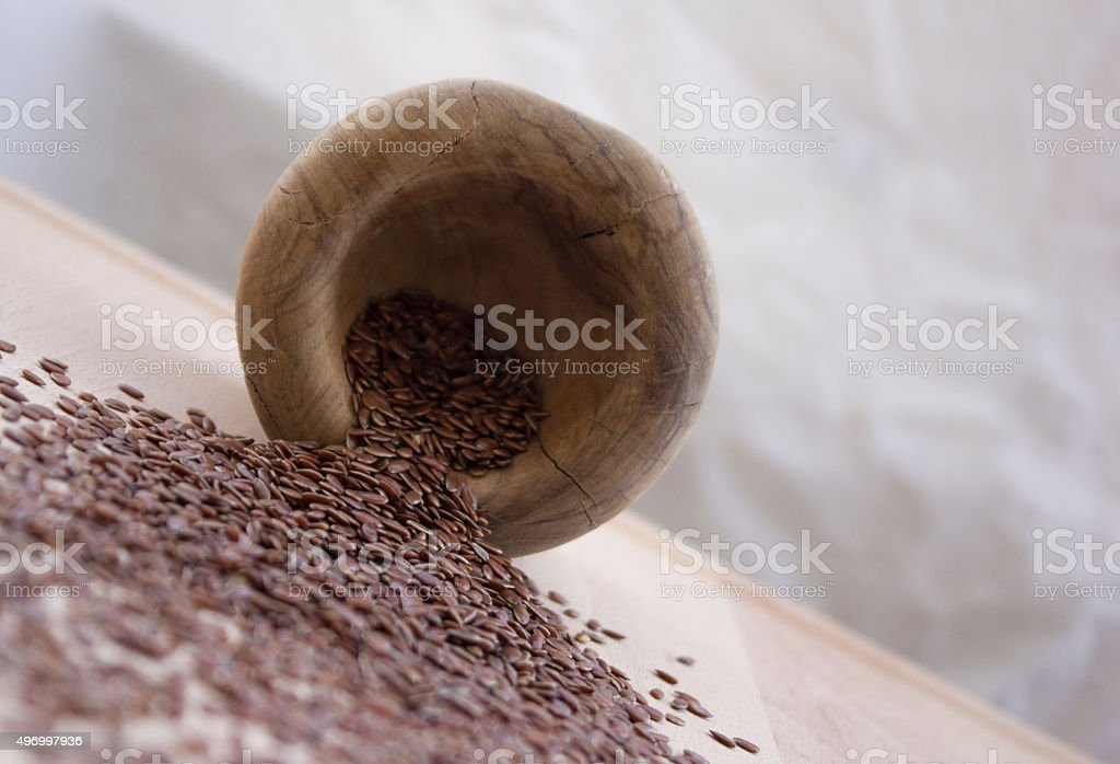Healthy flax seeds on wooden plate from olive wooden bowl stock photo
