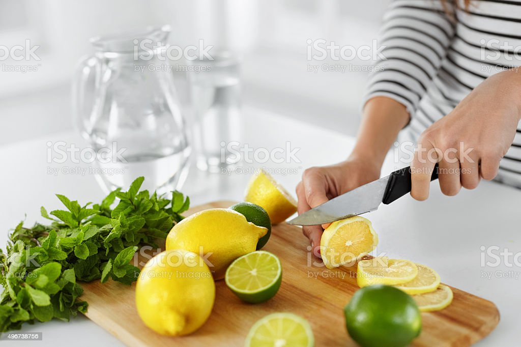 Healthy Food And Eating. Closeup Of Woman Kitchen Cutting Lemons stock photo