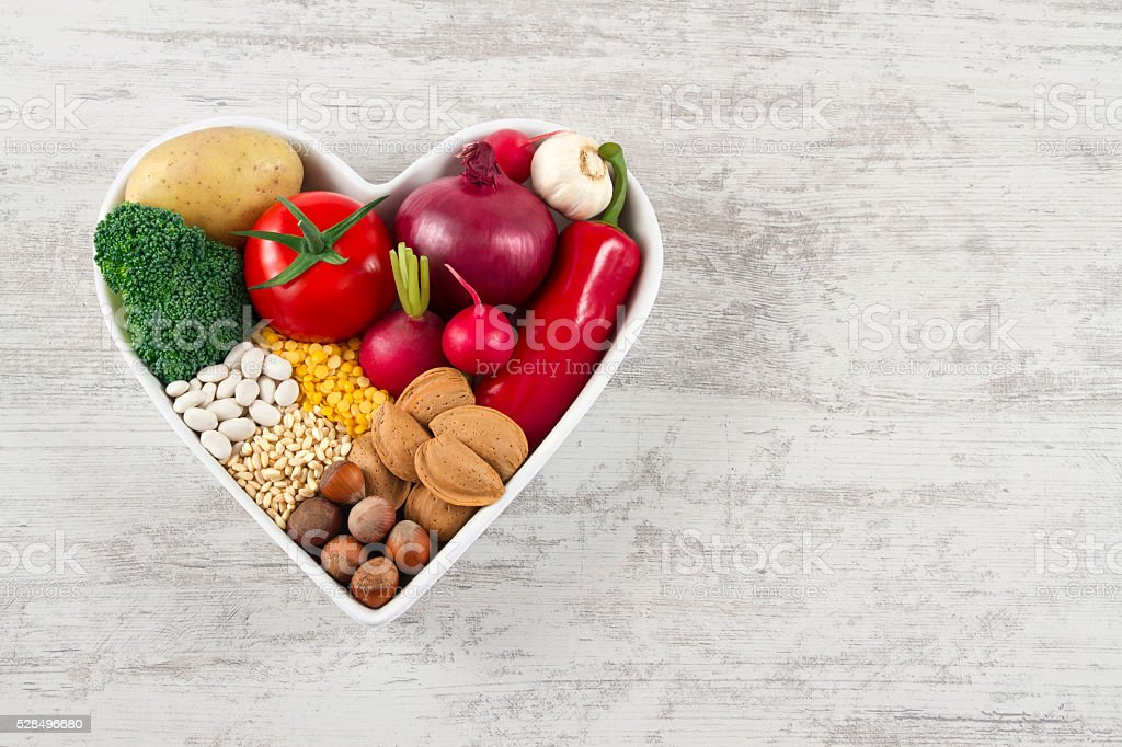 Healthy Foods in Heart Shaped Bowl on White Wooden Table stock photo