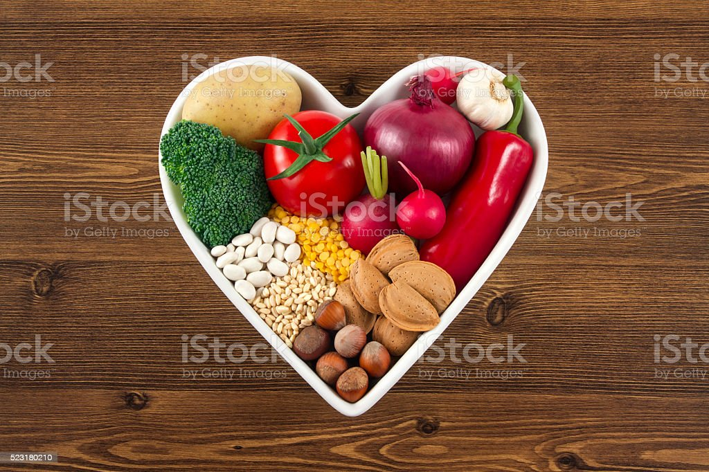 Healthy Foods in Heart Shaped Bowl on Wooden Background stock photo