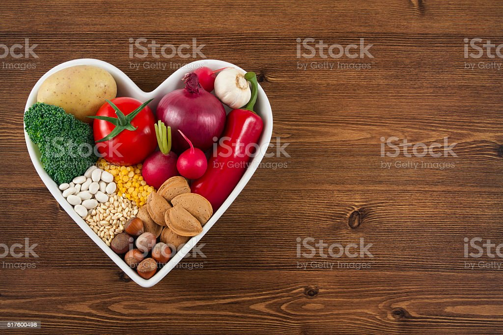 Healthy Foods in Heart Shaped Bowl on Wooden Table stock photo