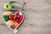 Healthy Foods in Heart Shaped with Stethoscope on Wooden Background