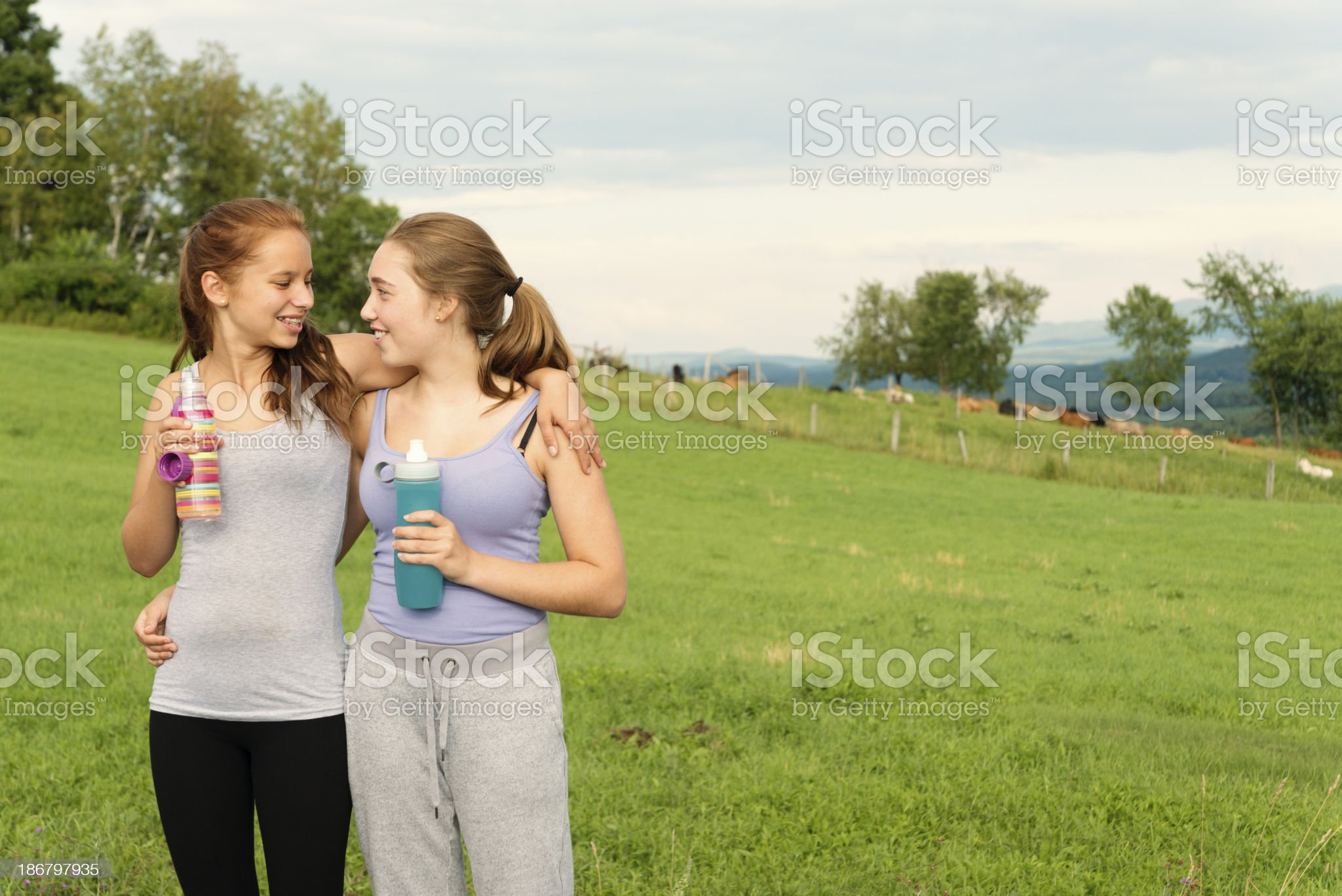 Healthy fresh girls with water bottle in nature after exercising. royalty-free stock photo