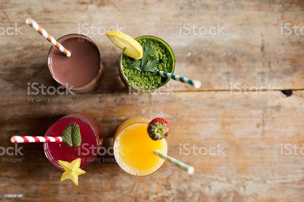 Healthy fresh smoothies with colorful striped straws stock photo
