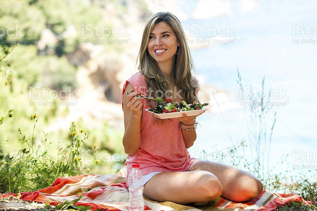 Saine jeune femme ayant la salade de pique-nique. photo libre de droits