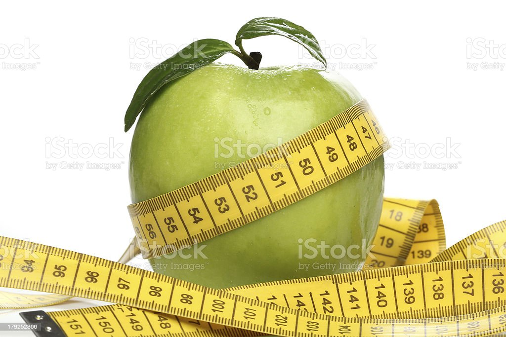 Healthy green apple and a measuring tape isolated royalty-free stock photo