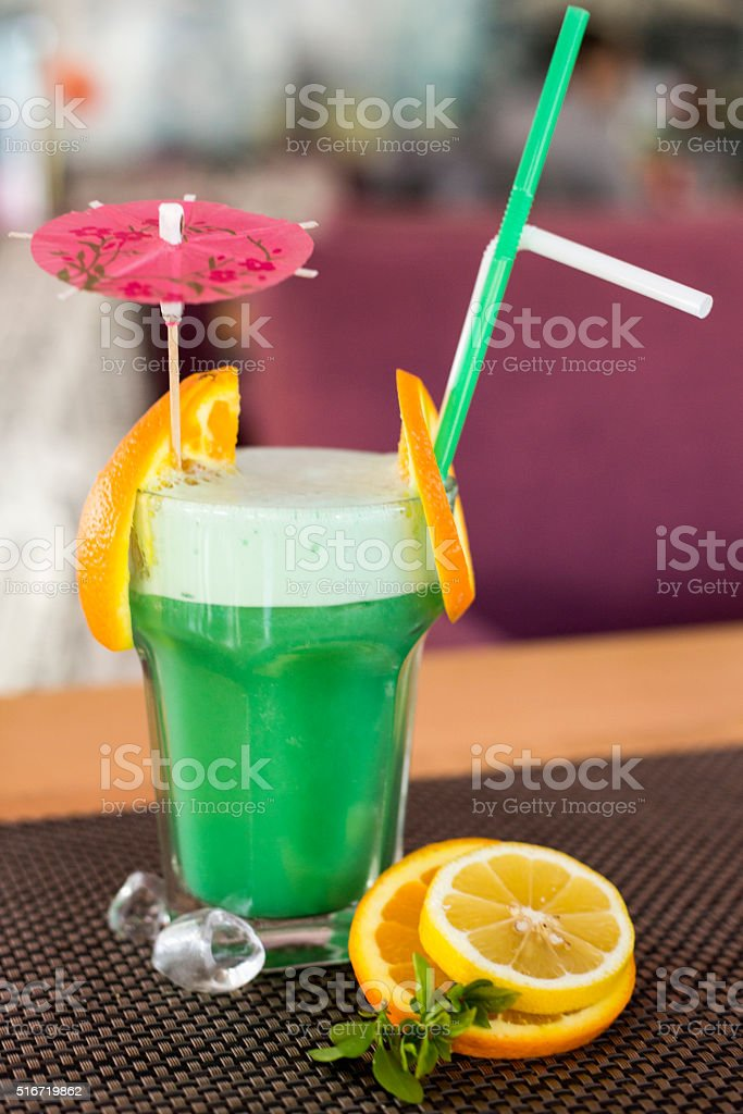 Healthy green smoothie with pieces of orange stock photo