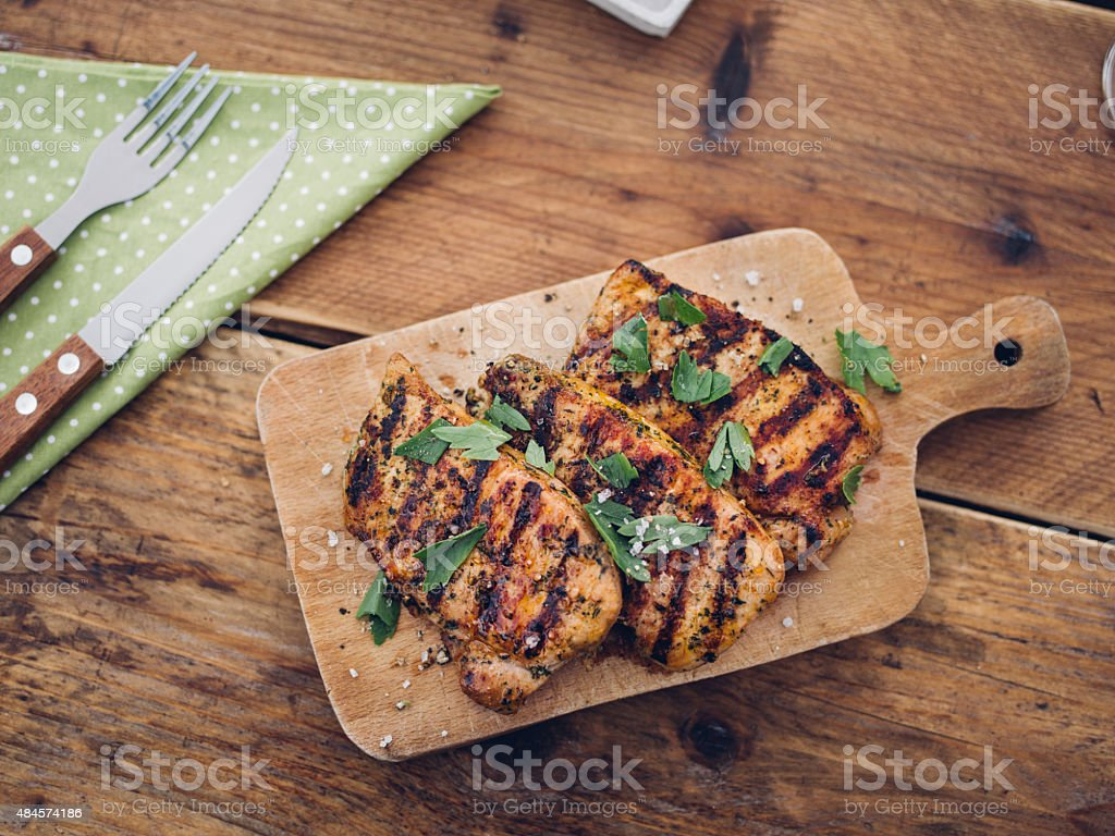 Healthy grilled pork fillets sprinkled with fresh herbs stock photo