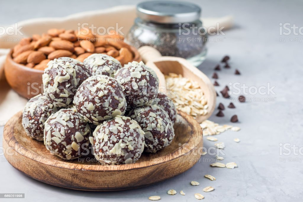 Healthy homemade paleo chocolate energy balls with rolled oats, nuts, dates and chia seeds, horizontal, copy space stock photo