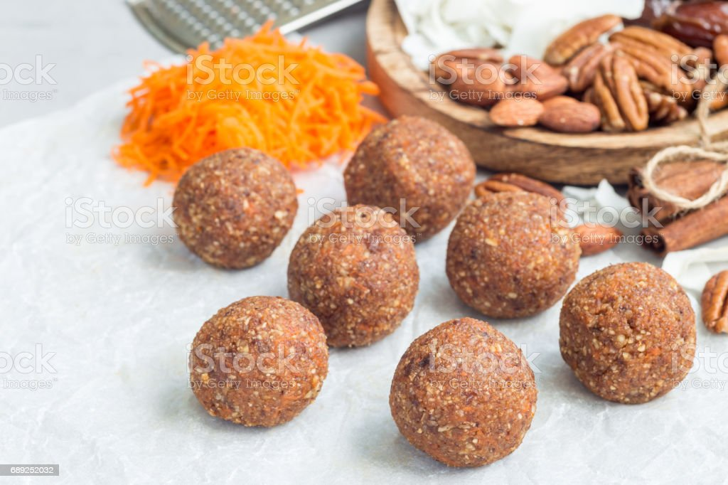 Healthy homemade paleo energy balls with carrot, nuts, dates and coconut flakes, on parchment, horizontal, copy space stock photo