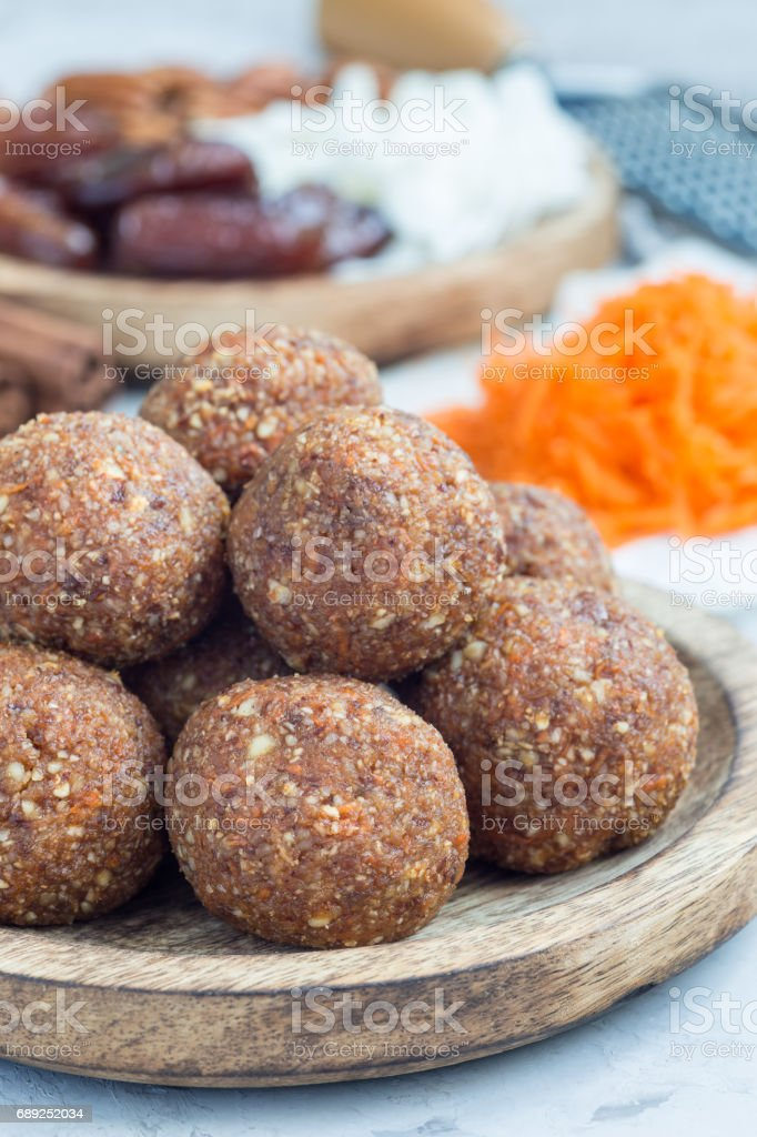 Healthy homemade paleo energy balls with carrot, nuts, dates and coconut flakes, on wooden plate, vertical stock photo