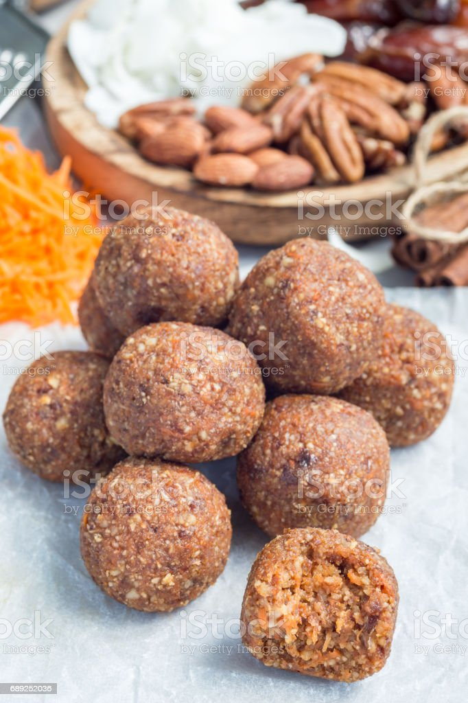 Healthy homemade paleo energy balls with carrot, nuts, dates and coconut flakes, on parchment, vertical stock photo